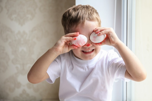 A four-year-old boy in a white t-shirt and a painted nose is fooling around trying on easter eggs on his eyes.