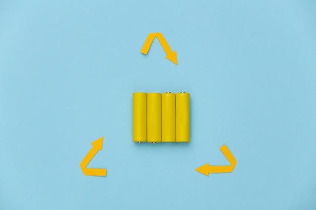 Четыре желтые батарейки типа аа с символом рециркуляции на синем пастельном фоне. вид сверху