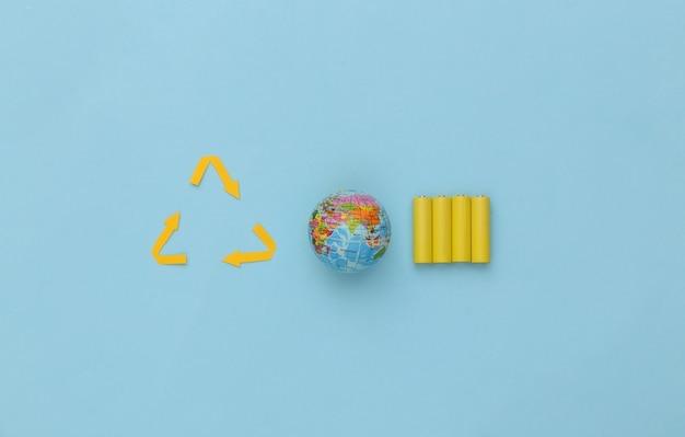 Четыре желтые батарейки аа со знаком переработанных стрелок, глобус на синем фоне. эко, спасти концепцию планеты. вид сверху