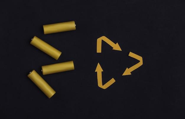 Четыре желтые батарейки типа аа с переработанными стрелками подписывают на черном фоне. вид сверху