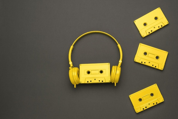 Four yellow cassettes with magnetic tape and yellow headphones on a gray background. color trend. vintage equipment for listening to music. flat lay.