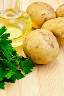Четыре желтых картофеля, пучок петрушки, растительное масло в бутылке на фоне деревянных досок