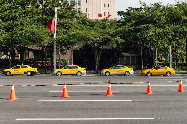 Four yellow taxis waiting for customers along the street that near the park with orange traffic cones.