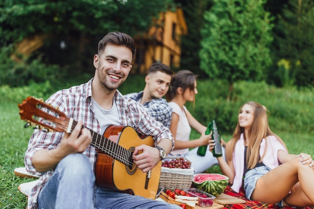 Four young attractive person chiiling in the park and one of them play at guitar and smilling.