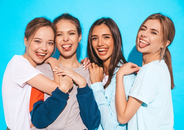 Four young beautiful smiling hipster girls in trendy summer clothes. sexy carefree women posing near blue wall in studio. positive models having fun and hugging.they show tongues