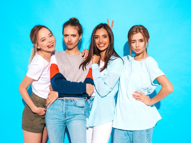 Four young beautiful smiling hipster girls in trendy summer clothes. sexy carefree women posing near blue wall in studio. positive models having fun and hugging