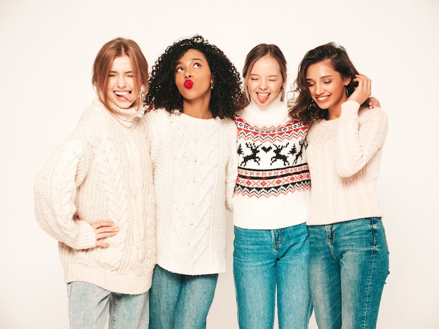 Four young beautiful smiling hipster girls in trendy winter sweaters. positive models having fun and hugging