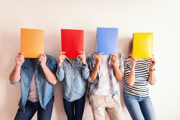 Four young business people standing against the white wall and holding folders in front of their faces.