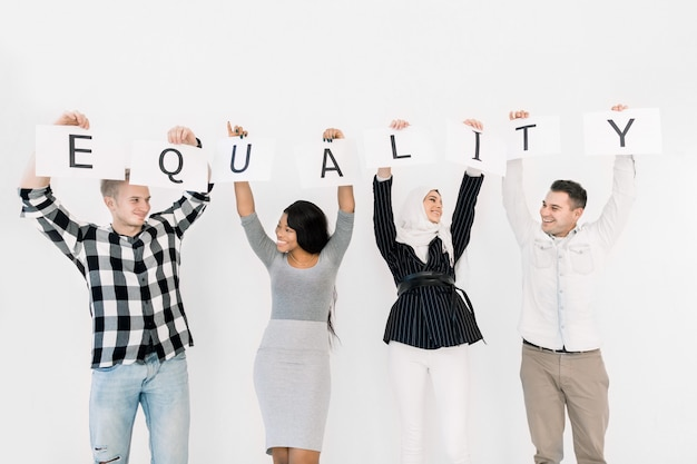 Four young diverse people of different races hold together paper posters with letters of the word equality, looking each other and smiling