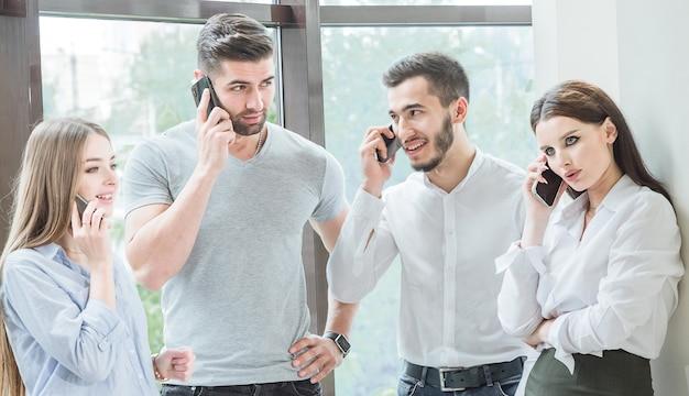 4人の若い従業員2人の男性と2人の女性の従業員がカジュアルな会話でコミュニケーションします
