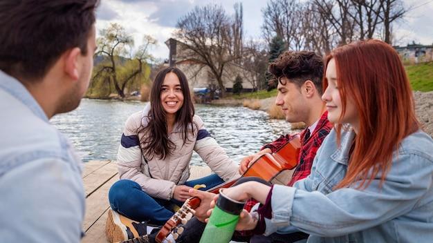 Quattro giovani amici cantano, riposano e suonano la chitarra vicino a un lago in un parco
