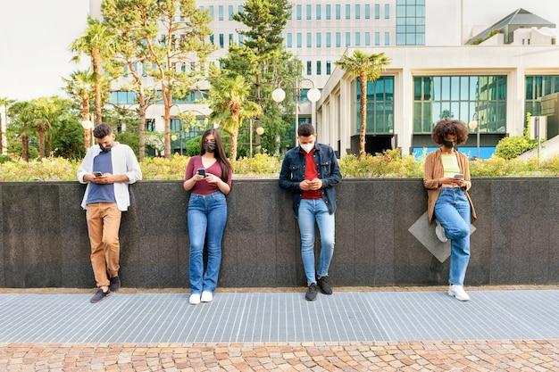 Четверо молодых друзей в масках и социальное дистанцирование во время пандемии covid-19 стоят в очереди на улице, прислонившись к низкой стене, увлеченные своими мобильными телефонами, игнорируя друг друга.