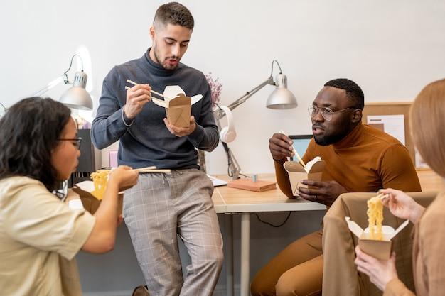 4명의 젊은 이문화 직장인들이 점심으로 중국 웍을 먹고 있다