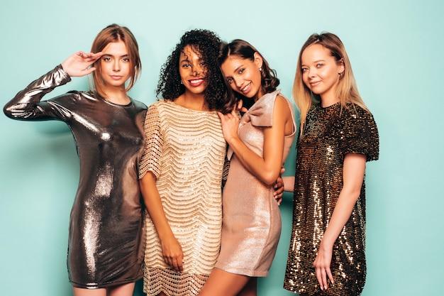 Четыре молодых международных красивых брюнетки в модном летнем блестящем платье.