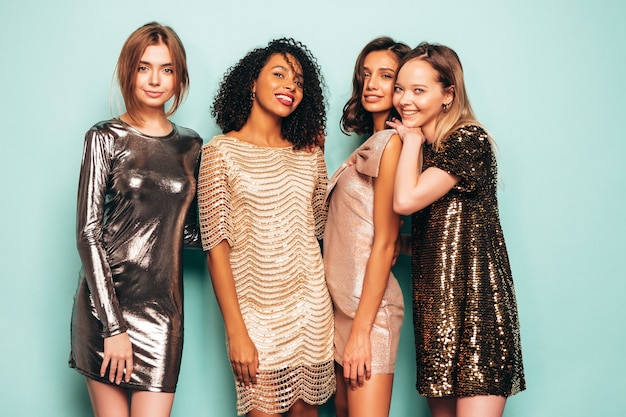 トレンディな夏の光沢のあるドレスを着た4人の若い国際的な美しいブルネットの女性。
