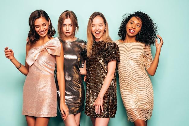 Quattro giovani belle donne castane internazionali in abito lucido estivo alla moda.