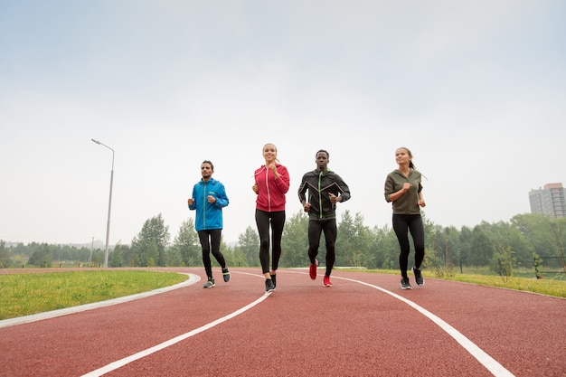 Four young male and female athletes in sportswear running marathon on racetracks of outdoor stadium