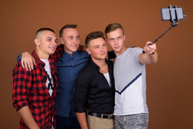 Четверо друзей молодых людей используют селфи-палку с мобильным телефоном, чтобы сфотографироваться