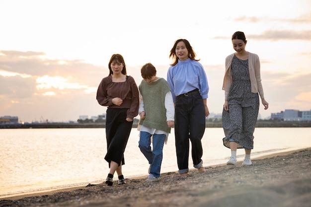 Четыре молодые женщины гуляют по морю в сумерках