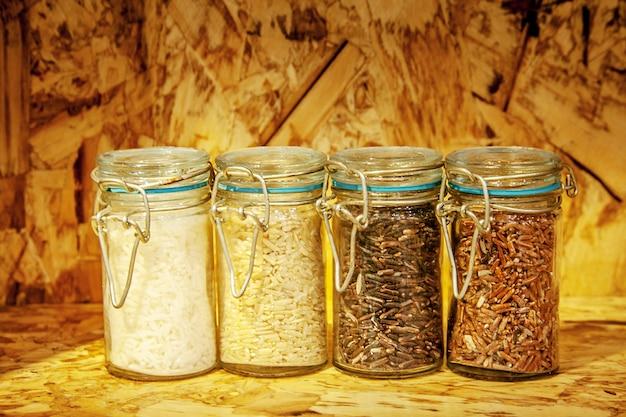 Foure раса сортов риса в стекле: коричневый рис, смешанный дикий рис, рис жасмина, рисовое зерно на деревянной полке