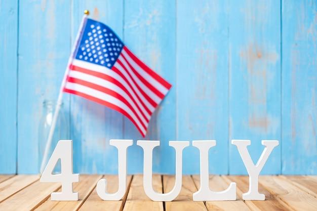 7月4日のテキストと木製のテーブルの背景にアメリカ合衆国の旗。独立とお祝いの概念の米国の休日
