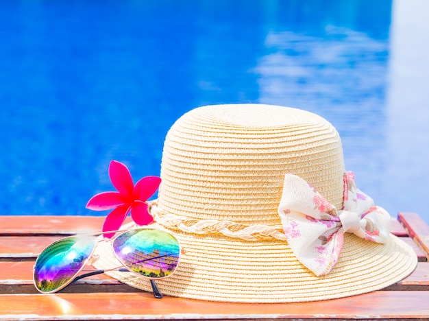 Fower with summer hat and sunglasses by the swimming pool