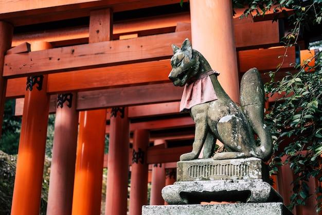 Скульптура лисы с красными воротами тории в храме фусими инари тайся в киото, япония
