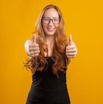 Закройте вверх по фото довольно foxy дамы поднимая большой палец руки вверх выражая носку согласования checkered вскользь изолированная рубашкой желтая стена цвета. рыжая девушка. ладно.
