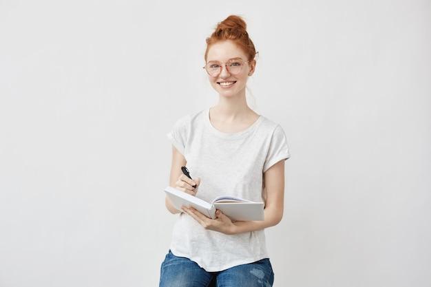 Foxy студентка, улыбаясь, держа ноутбук.
