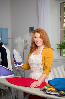 Foxy haired female at home ironing.