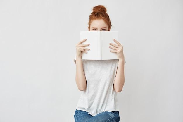 Foxy woman hiding face behind book.
