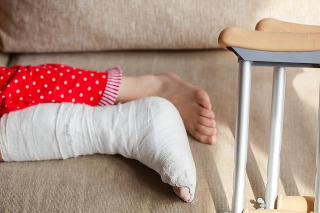 깁스와 목발을 든 10대 소녀 환자의 발목 뼈 골절. 외과 재활 및 정형 외과 회복, 소파에 누워, 집에 머물기