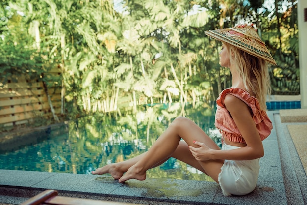 A fragile blonde girl is sitting in an asian hat near the pool. rest in hot countries