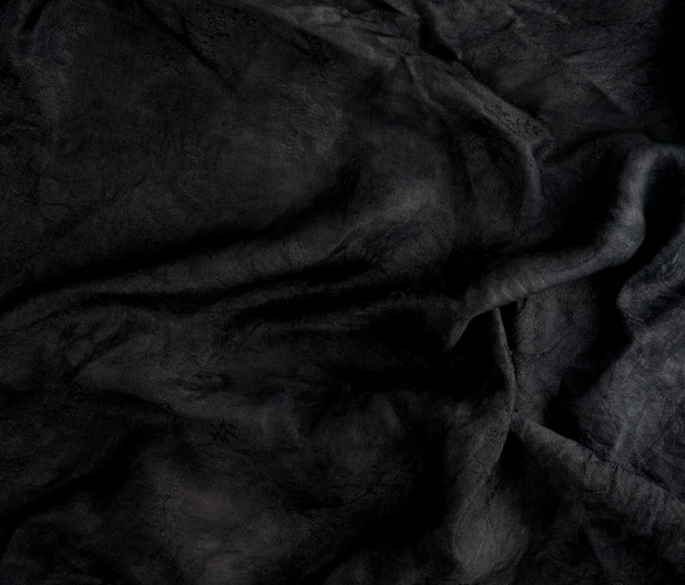 Fragment of black cotton fabric with waves