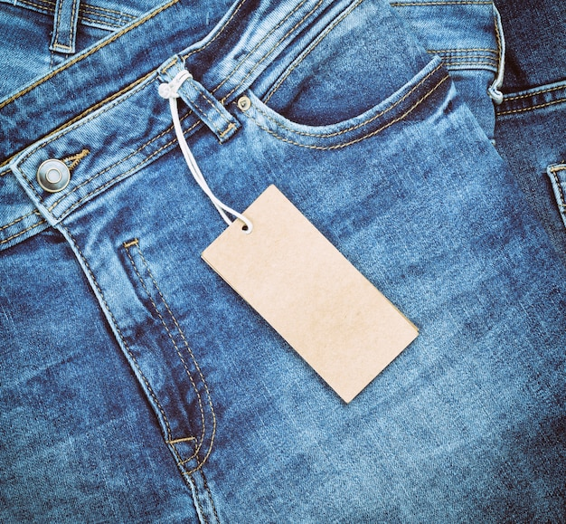 Fragment of blue jeans with a brown paper tag