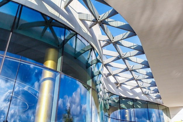 Fragment of curved glass facade of modern building in sunlight on a blue sky background