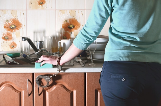 Fragment of the female body, handcuffed to the kitchen counter