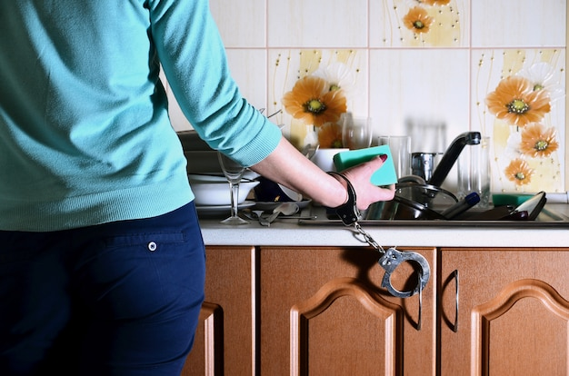 Fragment of the female body, handcuffed to the kitchen counter,