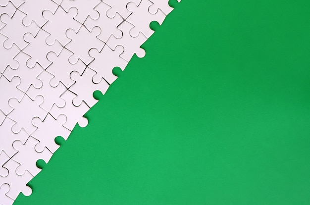 Fragment of a folded white jigsaw puzzle on the background of a green plastic surface