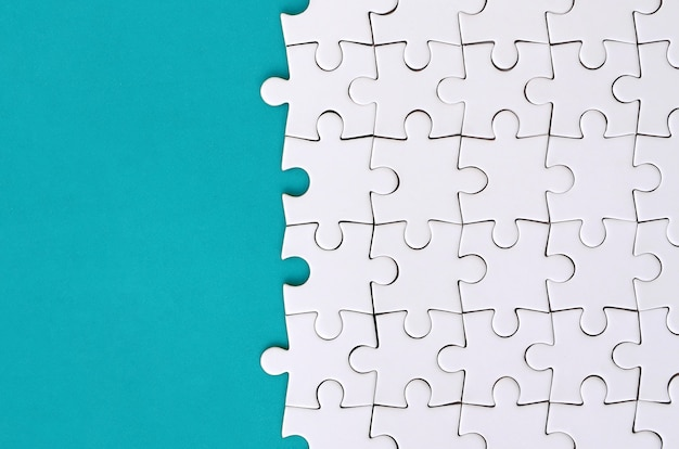 Fragment of a folded white jigsaw puzzle on blue plastic surface.