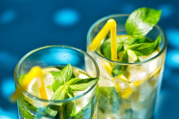 Fragment of glasses of lemonade on blue background