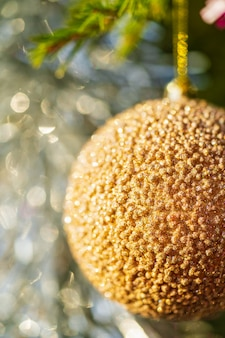Fragment of golden christmas ball hanging on branch of tree. close-up view of xmas festive composition for happy new year. selective focus in foreground, blurry bokeh in background.