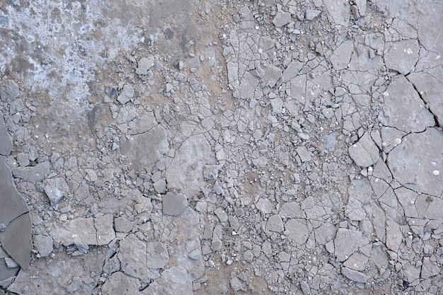 Fragment of gray cracked cement floor