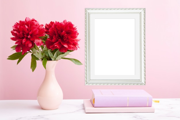 Fragment of an interior with an empty photo frame, a vase with peonies and books
