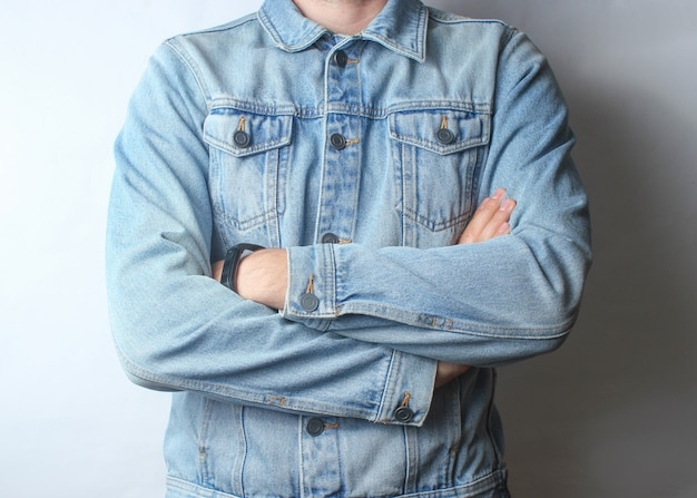 Fragment of a man dressed in a denim jacket and beige trousers.