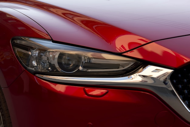 Fragment of a modern red car, headlight and bumper. close up