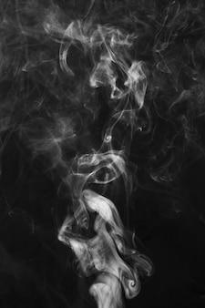 黒い背景に白い煙の片の動き