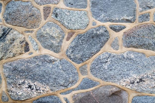 색깔, 질감 돌담의 조각입니다. 자연석과 시멘트로 만든 벽. 밝은 배경. 공간 복사, 텍스트 배치