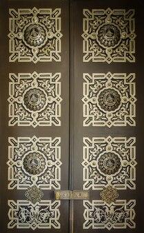 Фрагмент двери в восточном стиле с орнаментом и арабской графикой.