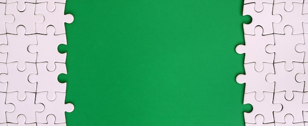 녹색 플라스틱 표면의 배경에 접힌 흰색 직소 퍼즐의 조각